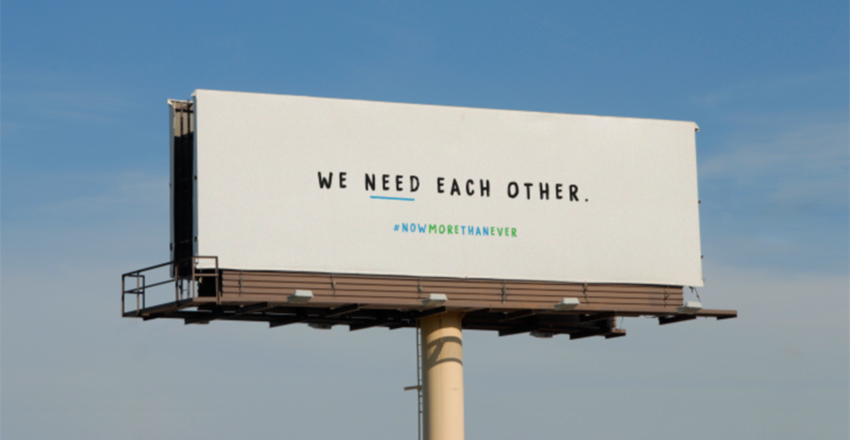 Highway billboard with Cox message - We Need Each Other in center - #NowMoreThanEver