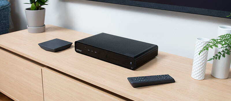 Cox Contour Stream Player box and remote on credenza with tv on wall in background